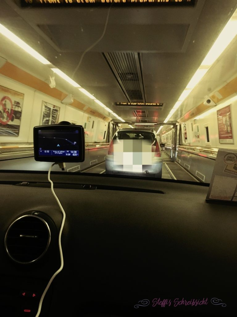 Auch hier gab es eine sehr gute Beschilderung und wir konnten unsschnell auf dem Gelände des Eurotunnels zurecht finden. Das Kennzeichen unseres Autos wurde an einer Schranke gescannt und wir konnten uns an einem Touchscreen aussuchen, ob wir schon mit einem früheren Zug fahren möchten. Das nahmen wir natürlich gerne an und es wurde ein Ticket ausgedruckt, das wir gut sichtbar an den Rückspiegel hängen mussten.